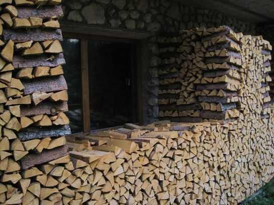 сложенные штабелем дрова возле дома